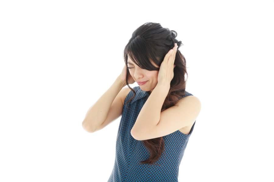 辛く頭を抱える女性