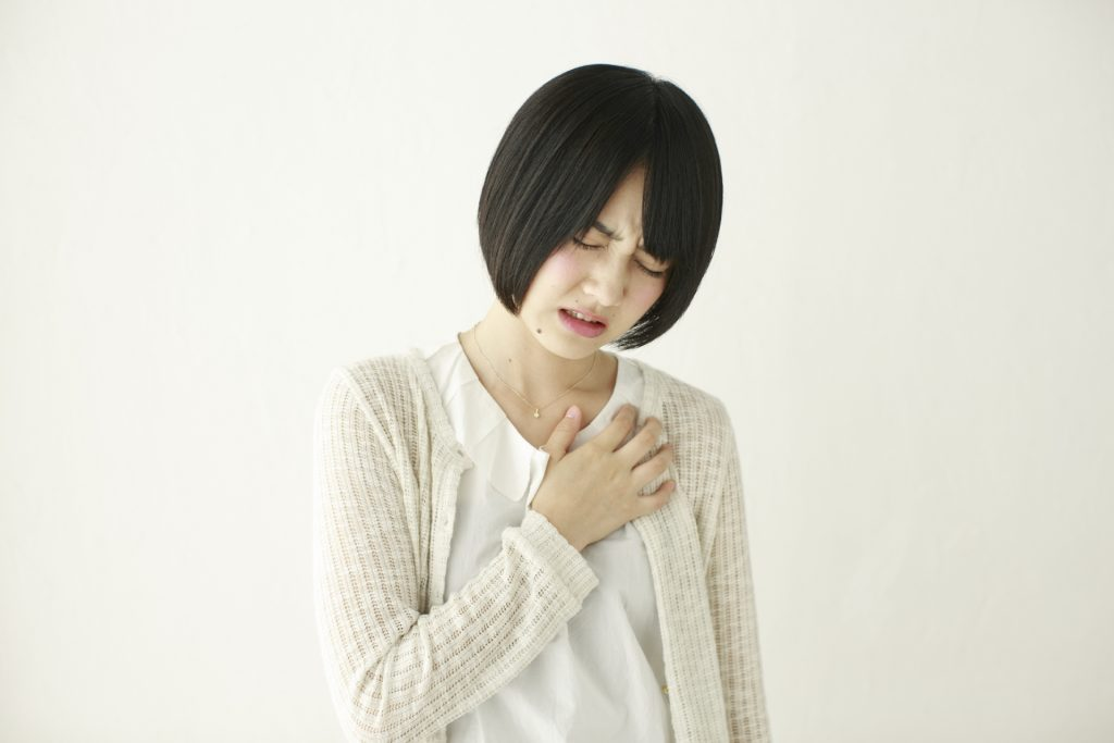 胸を抑えている女性