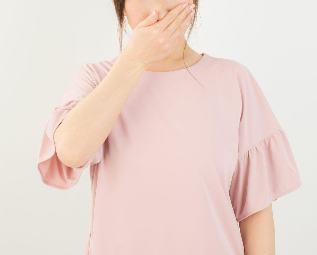 口を押さえている女性