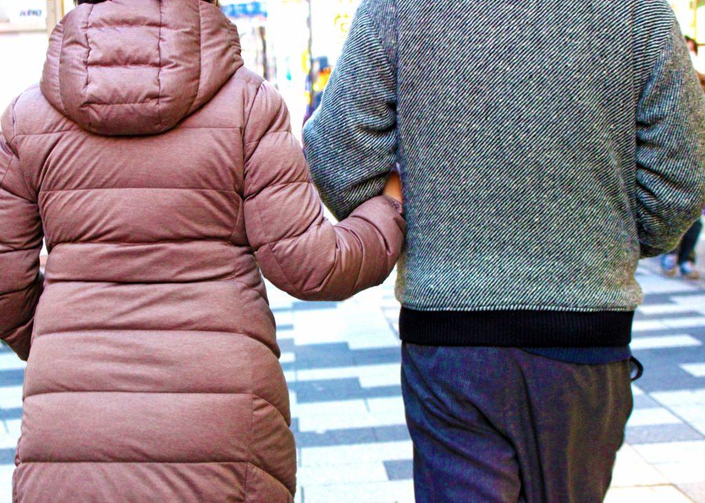 腕組みをしている夫婦