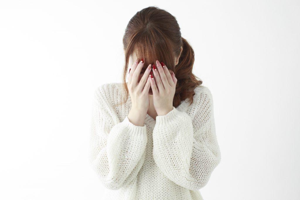 恥ずかしがって顔を隠している女性