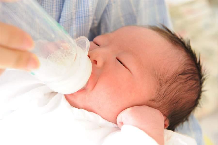 哺乳瓶を加えている赤ちゃん