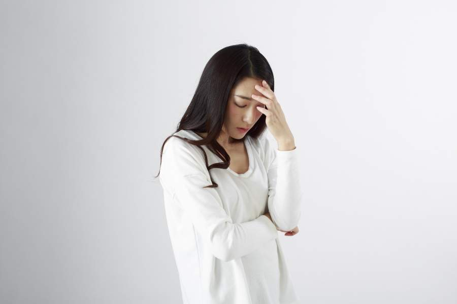頭を抑えている女性
