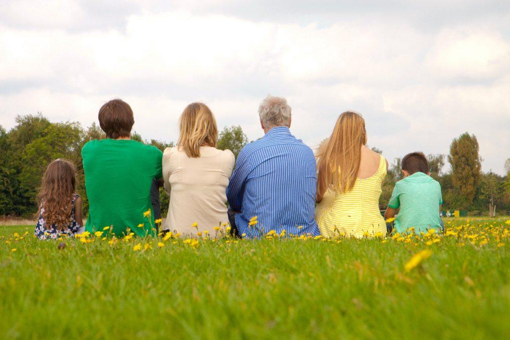 芝生の上で並ぶ家族