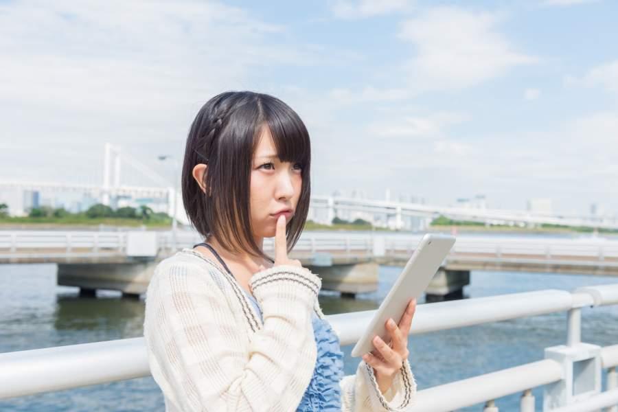 携帯を見て考えている女性