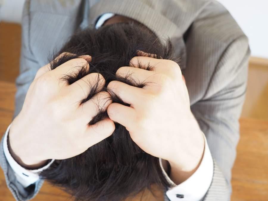 頭を抱えている男性