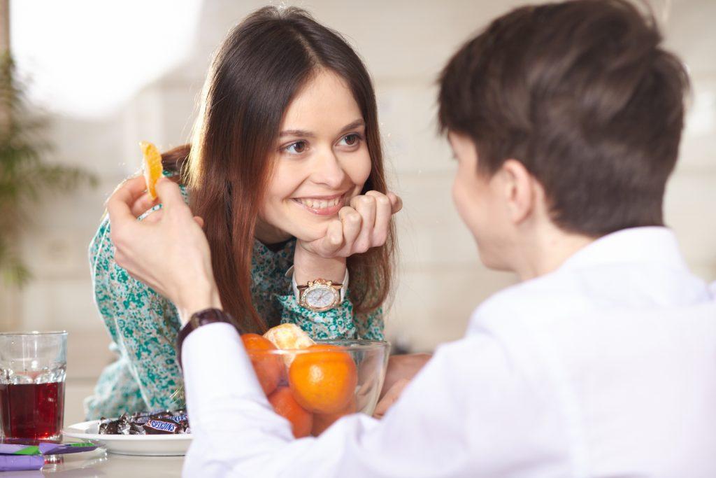 オレンジを食べるカップル